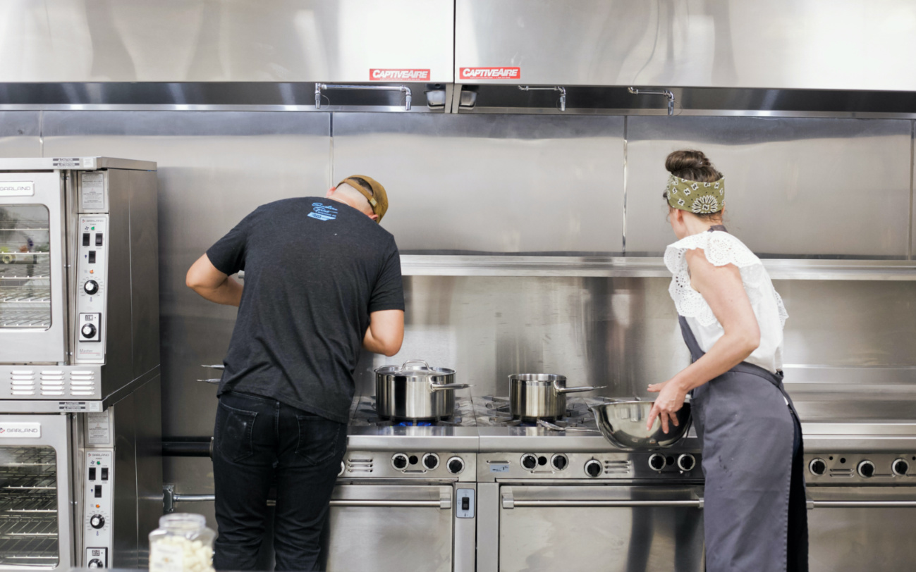Two food entrepreneurs cooking at the commercial kitchen space, Catapult Kitchen Incubator